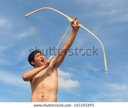 A young man shoots a bow. A man of Asian appearance