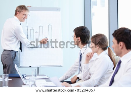 A young man shows a graph to colleagues - stock photo