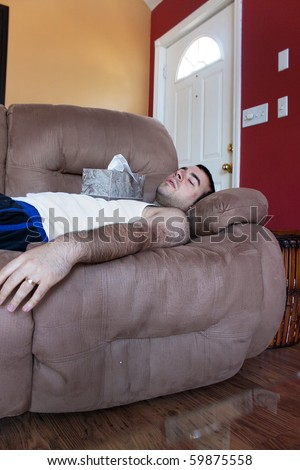 A young man sick on the couch with the tissue box on his chest. - stock photo