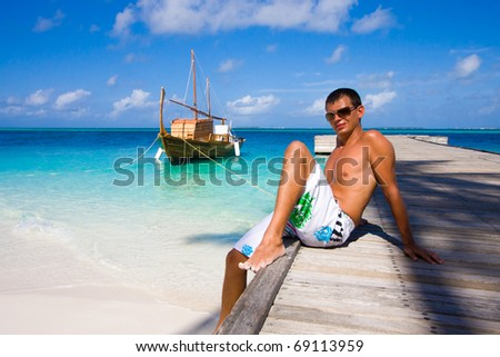 A young man sits on a pier - stock photo