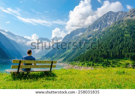 A young man sits on bench beside an azure mountain lake on the background of the high peaks of the Alps, Zillertal, Austria - stock photo