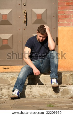 A young man sits on the stairs near the house