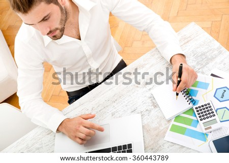 A young man sitting at the table with a laptop computer.
