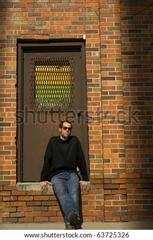 A young man sitting in an illuminated doorway of a brick building - stock photo