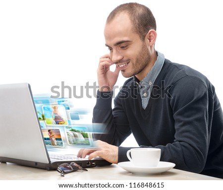 A young man sitting in front of a laptop and sharing photo and video files in social media resources using his computer isolated - stock photo