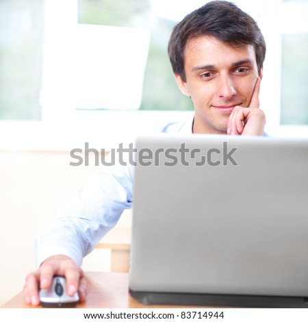 A young man sitting in front of a laptop at college library - stock photo