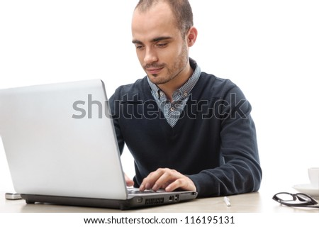 A young man sitting in front of a laptop isolated - stock photo