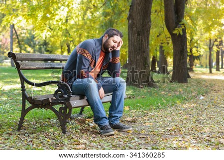 A young man sitting in the park with his hand on his head - stock photo