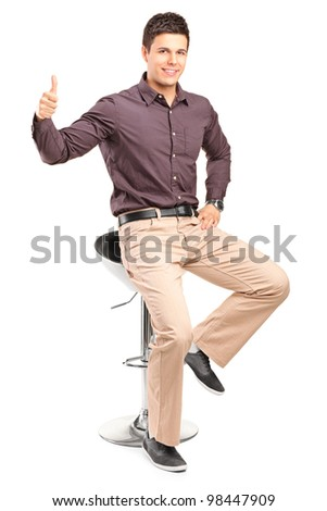 A young man sitting on high chair and giving thumb up isolated on white background - stock photo