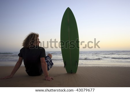 a young man sitting on the beach with his surfboard watching the sunset. - stock photo