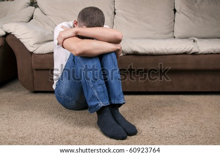 A young man sitting on the floor suffering from depression