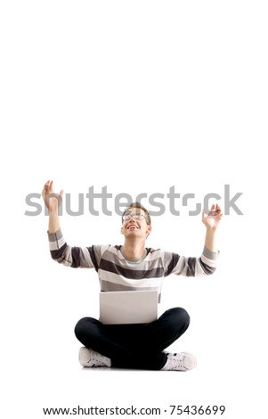 A young man sitting on the floor with a laptop, hands up - stock photo