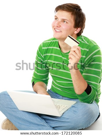 A young man sitting on the floor with a laptop, holding a credit card - stock photo