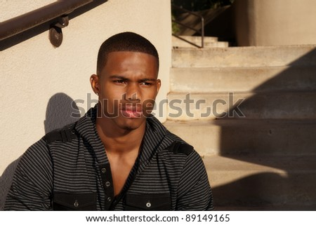 a young man sitting outside on a staircase with a serious expression