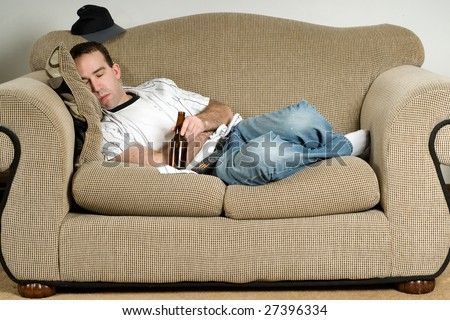 A young man sleeping on the couch with a bottle of beer - stock photo
