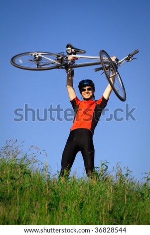 A young man smiling and holding a bicycle - stock photo