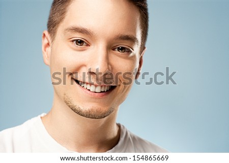 A young man smiling and posing in front of a blue background. - stock photo