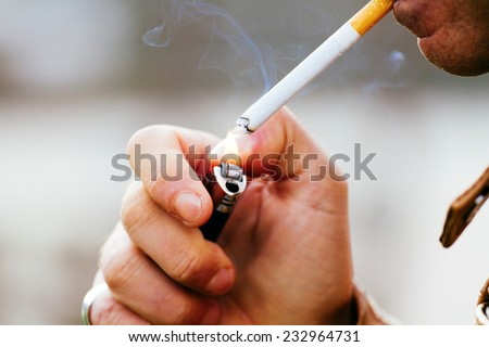 a young man smoking a cigarette - stock photo