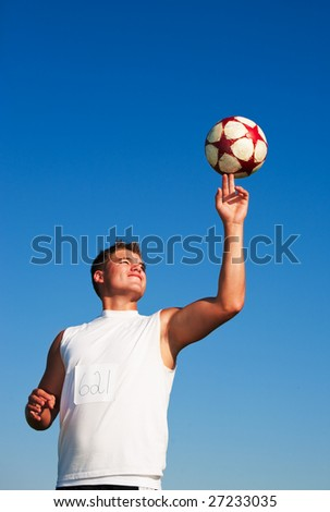 A young man spinning a soccer ball on his finger in the warm summer sun. - stock photo