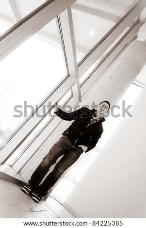 A young man standing by some large windows alone in sepia tone. - stock photo