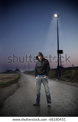 A young man standing in a street by night - stock photo