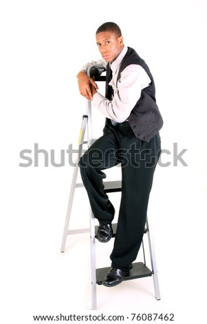 A young man standing on a ladder - stock photo