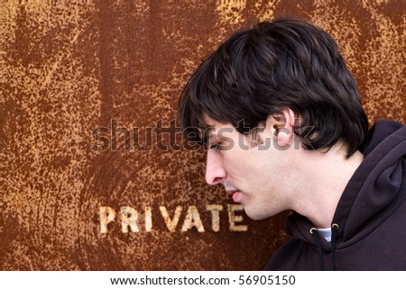 A young man standing outside an old door or entrance that reads PRIVATE.  A great image for any identity theft concept. - stock photo