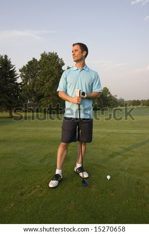 A young man, stands holding his golf club, staring off into the sunset. Vertically framed shot. - stock photo