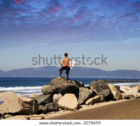 A young man stands on the coastline and checks surf conditions - stock photo