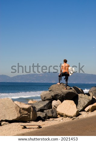 A young man stands on the coastline and looks at the surf condition. - stock photo