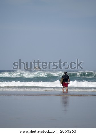 A young man stands on the coastline checking surf conditions a ship can be sought on the background - stock photo
