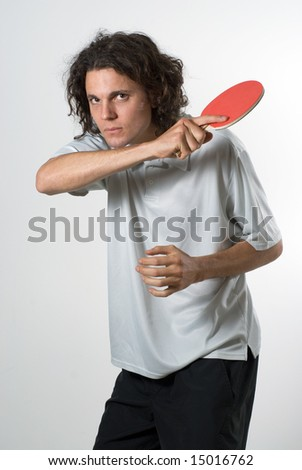 A young man, staring intently, swings a ping pong racket. Vertically framed shot. - stock photo