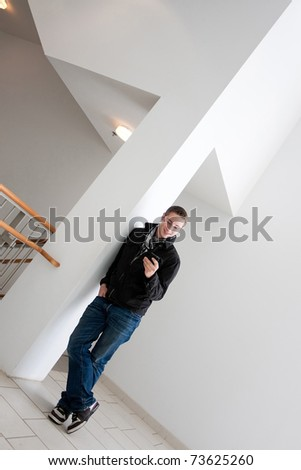 A young man stops to check his smart phone. - stock photo