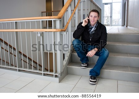 A young man stops to sit on the stairs and talk on his cell phone. - stock photo