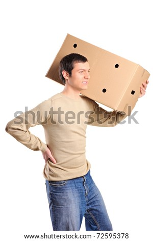 A young man suffering from back pain while lifting a large box isolated on white background - stock photo
