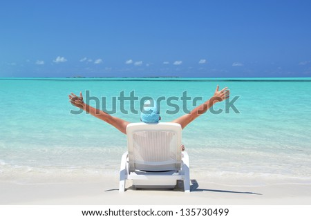 A young man sunbathing on the beach of Exuma, Bahamas - stock photo