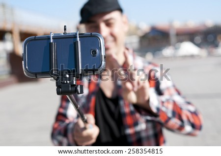 a young man taking a self-portrait with a selfie stick while gives a V sign - stock photo