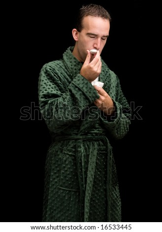 A young man taking his temperature and wearing a bathrobe - stock photo
