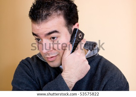 A young man talking on his cell phone.  He is holding the phone with his right hand but listening with his left ear. - stock photo