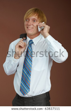 A young man talking on the phone on a brown background - stock photo