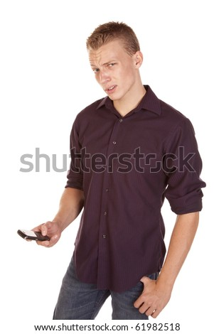 A young man texting on his phone with an confused expression on his face. - stock photo