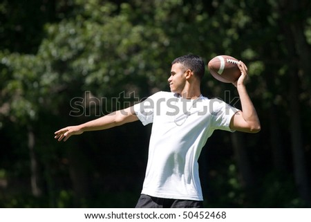 A young man throwing a football outdoors. - stock photo