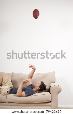 A young man tosses a football up on the couch. - stock photo