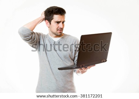 A young man touches his head wile working on his laptop