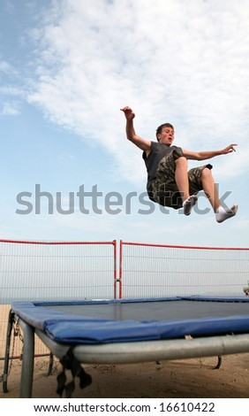 A young man trampolining on the beach at Great Yarmouth, England - stock photo