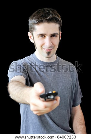A young man using a remote control on black background. - stock photo