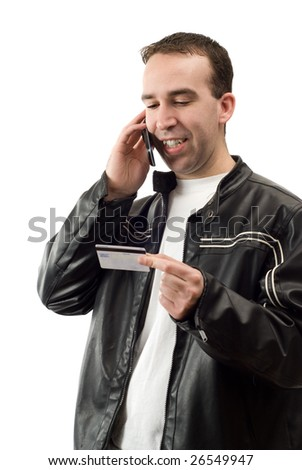 A young man using his credit card to pay for something on a cell phone, isolated against a white background - stock photo