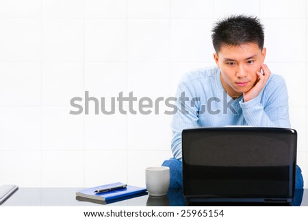 A young man using his laptop while leaning his head. - stock photo