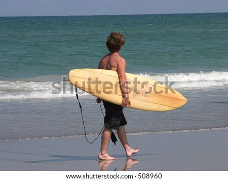 a young man walking along the beach with his surfboard