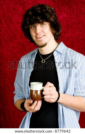 A young man warming up with a cup of hot chocolate.